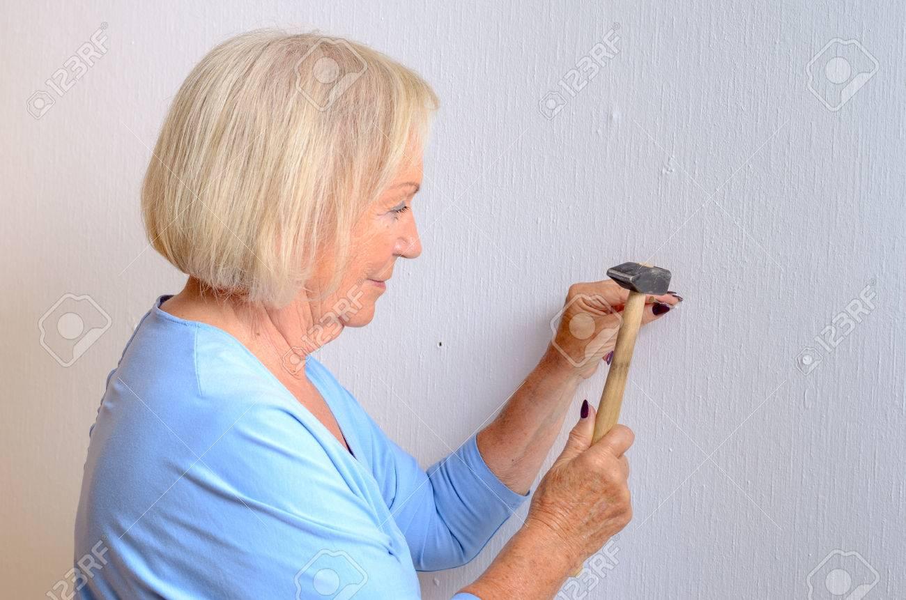Lächeln Fähig ältere Frau DIY Stehende Tun, Um Einen Nagel Und ...