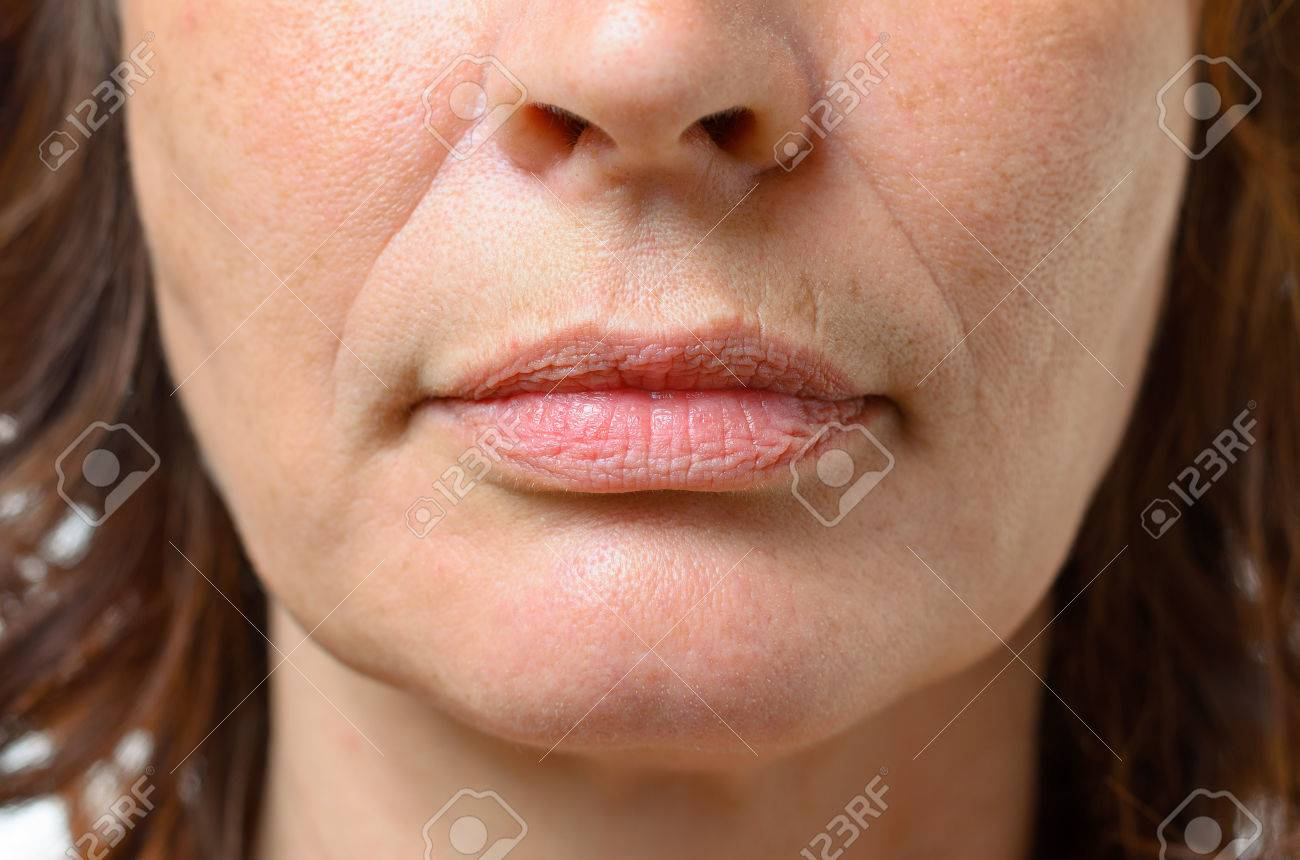 Closeup on the mouth of a middle-aged brunette woman with her mouth closed and a serious expression - 59848626