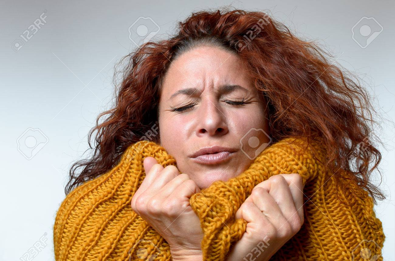 Cold young woman snuggling into a warm knitted woollen winter top with a grimace and her eyes closed as she tries to warm up, close up on white - 67102150