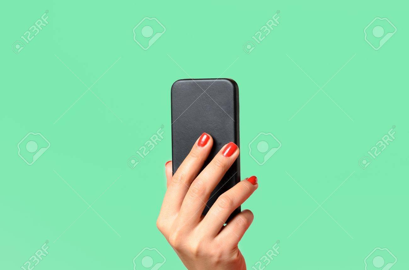 Mujer Joven Con Las Uñas Pintadas Rojas Que Sostienen Un Teléfono ...