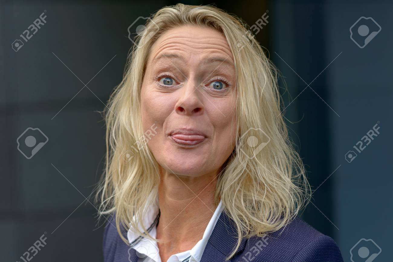 Playful Blond Woman Sticking Out Her Tongue With Raised Eyebrows