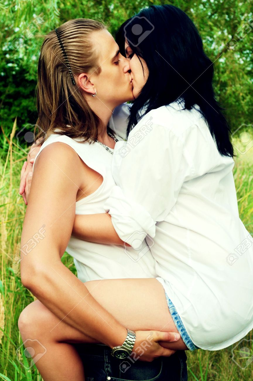 young man and woman kiss and hug one another in white clothes