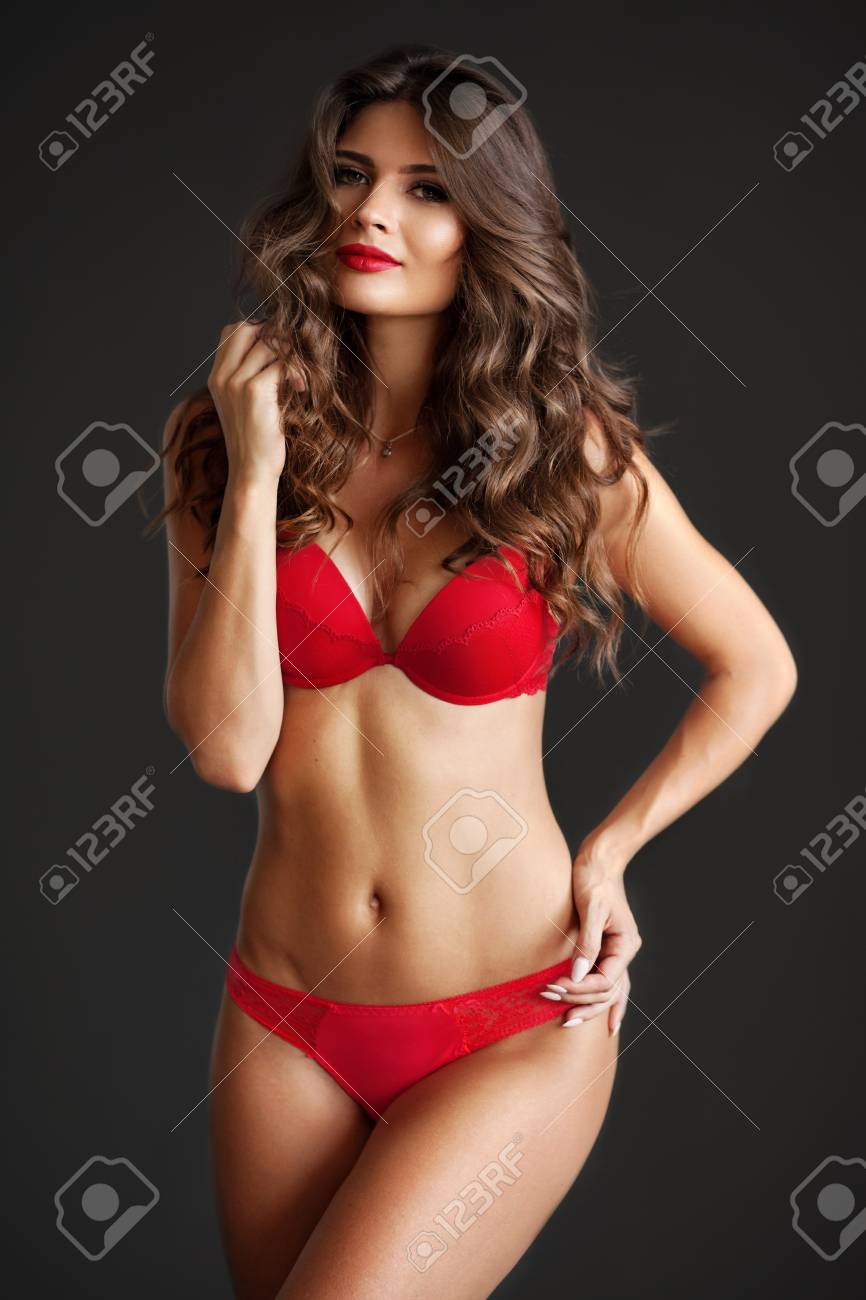c86ef0372 Pretty elegant lady in beautiful red lingerie against dark gray background  Stock Photo - 94812968