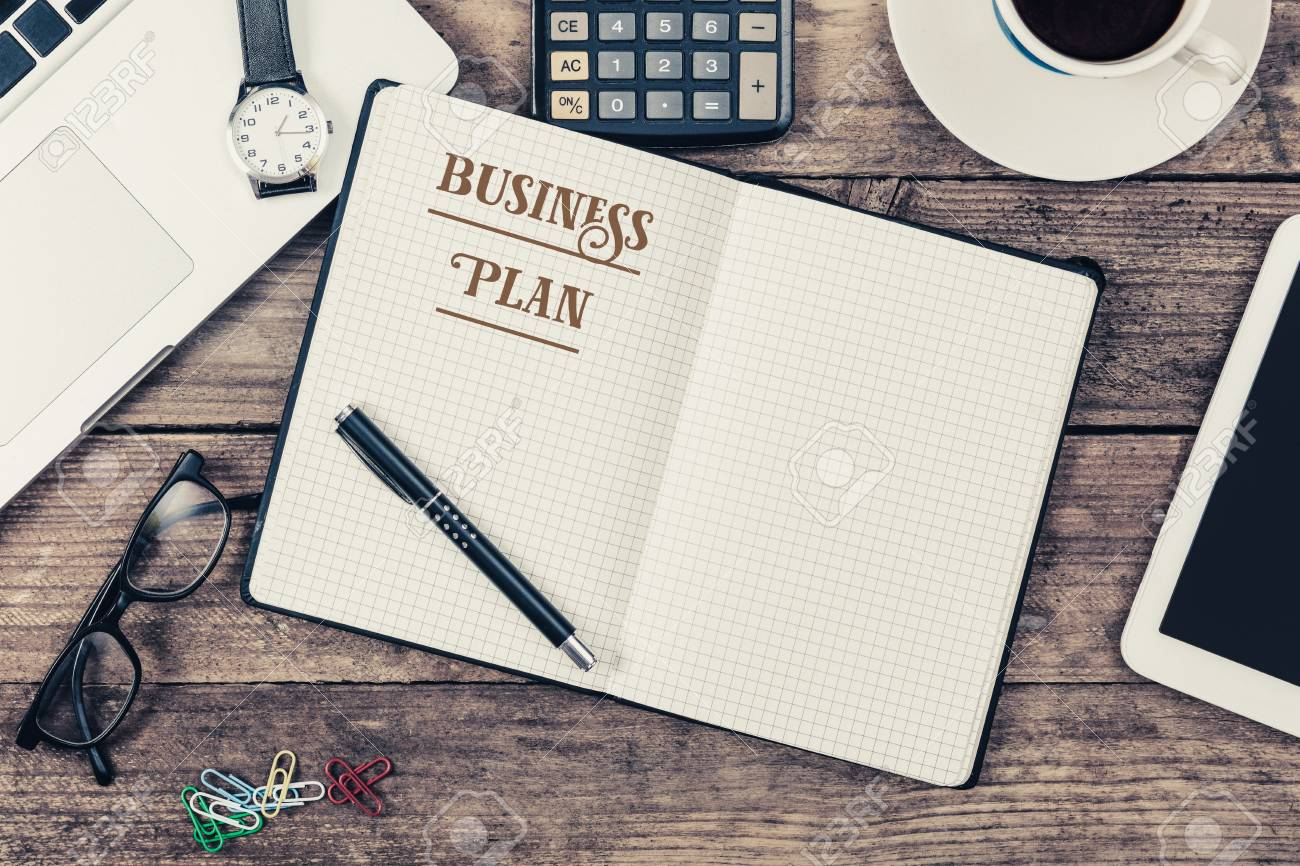 Business Plan Written In Note Pad, Office Desk With Electronic Devices,  Computer And Paper