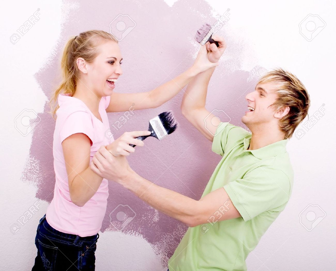 couple having fun while painting house stock photo picture and
