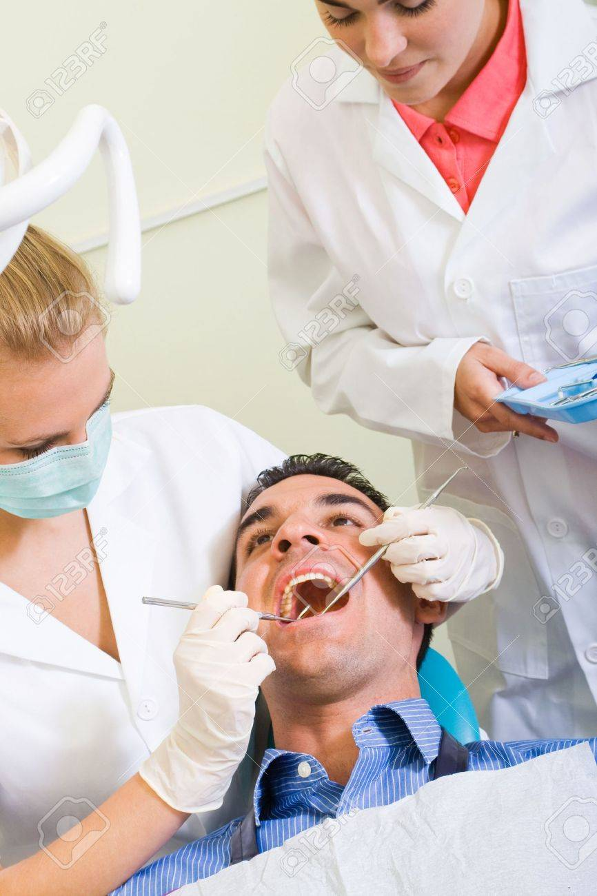 dentist and assistant working on male patient Stock Photo - 5715924