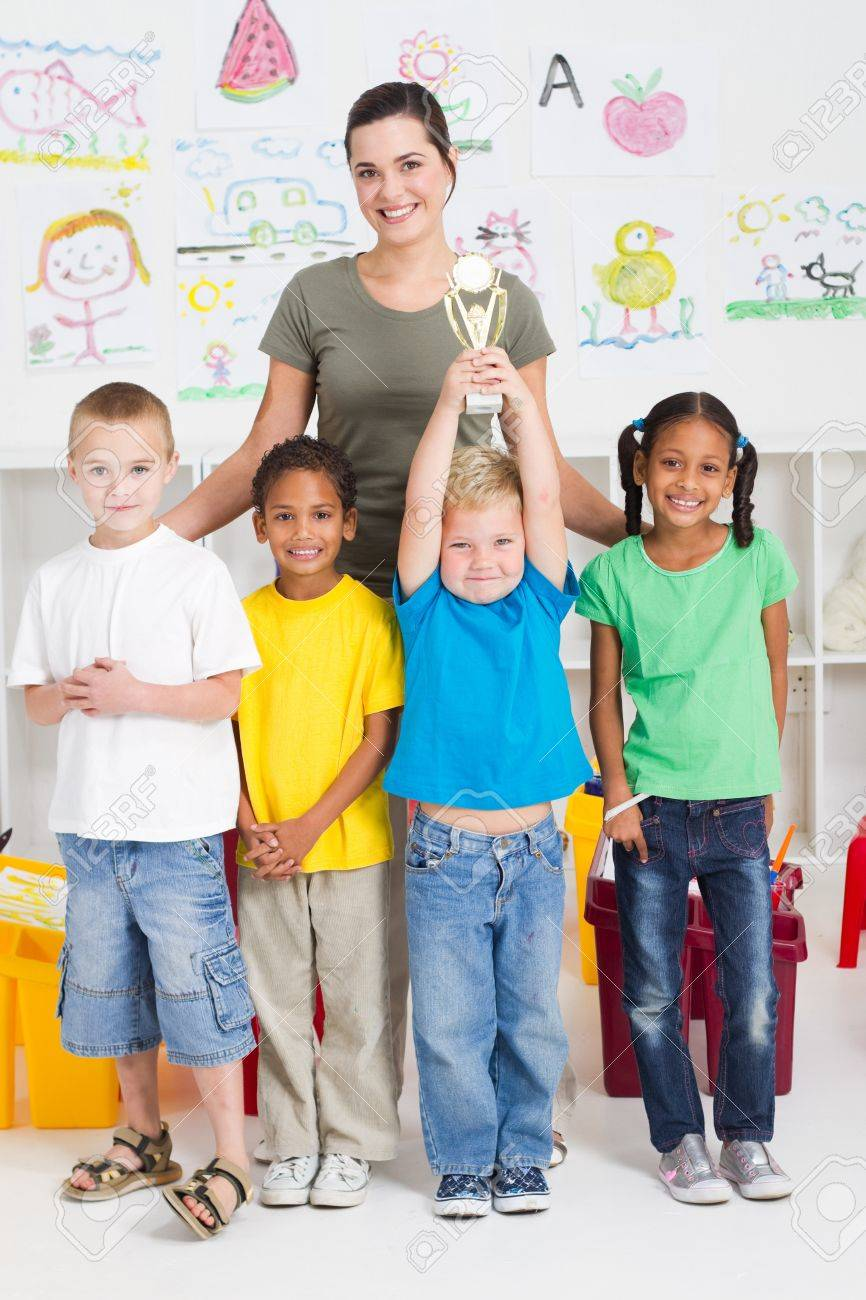 happy preschool boy holding trophy with classmates Stock Photo - 7795758