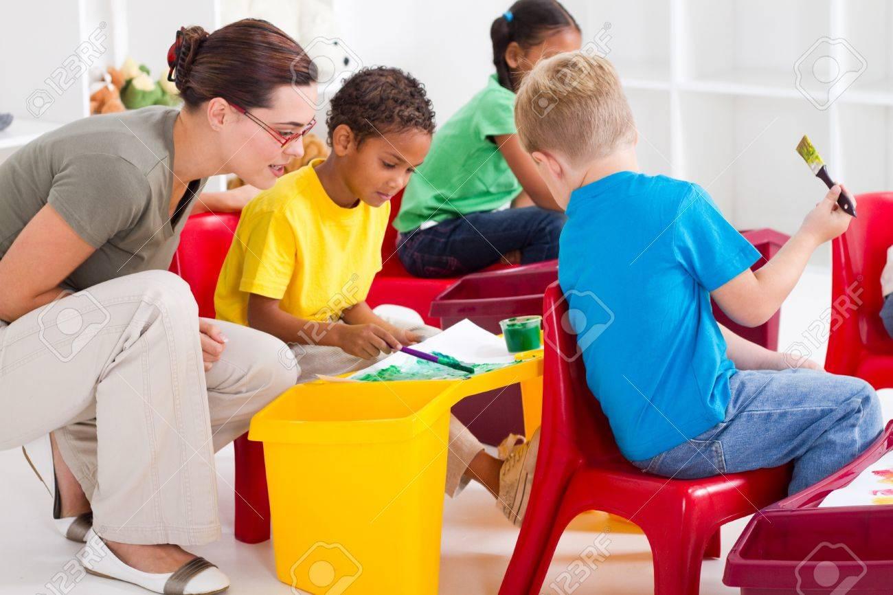 preschool teacher helping kids paint pictures Stock Photo - 7795733