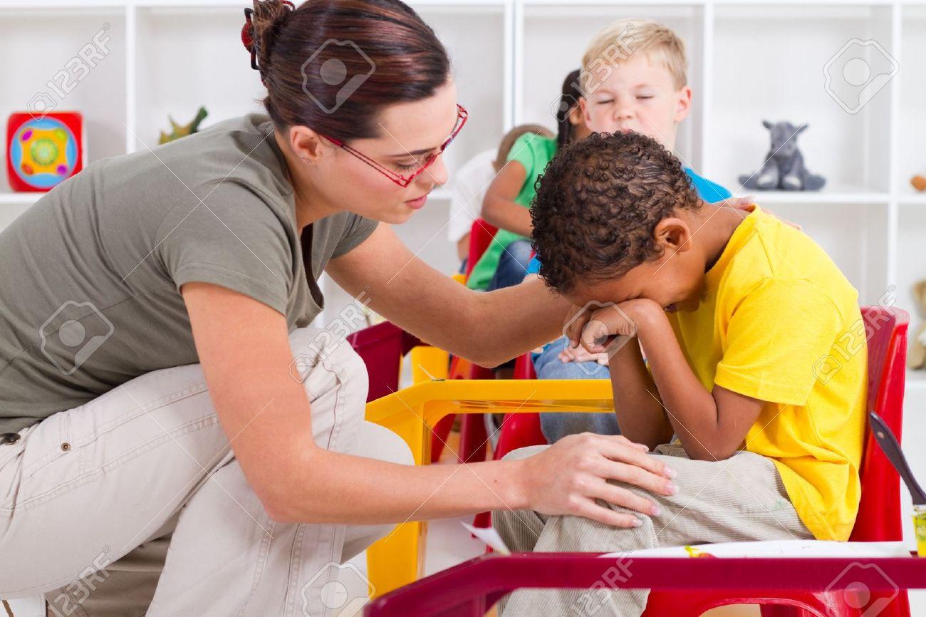 teacher comforting crying preschool boy Stock Photo - 7795721