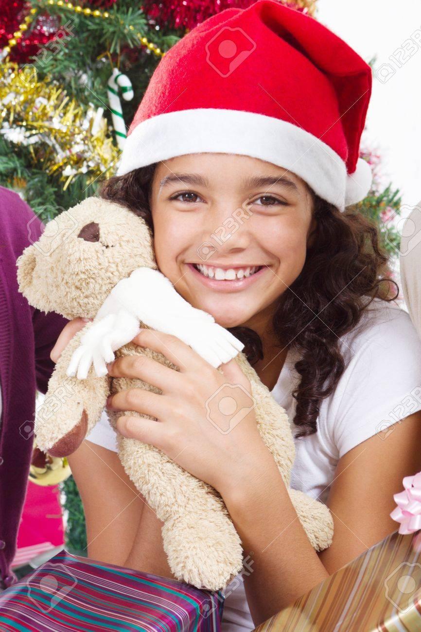 happy pre-teen girl hugging teddy bear under christmas tree Stock Photo - 8111846