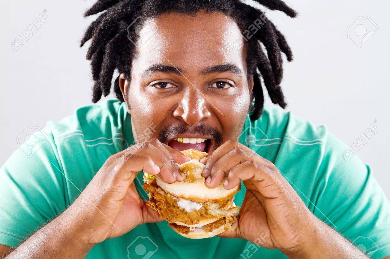 happy fat african american man eating a hamburger Stock Photo - 9844272