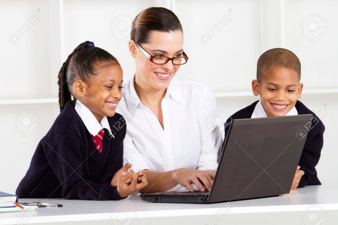 elementary teacher teaching computer class to students Stock Photo - 10747030