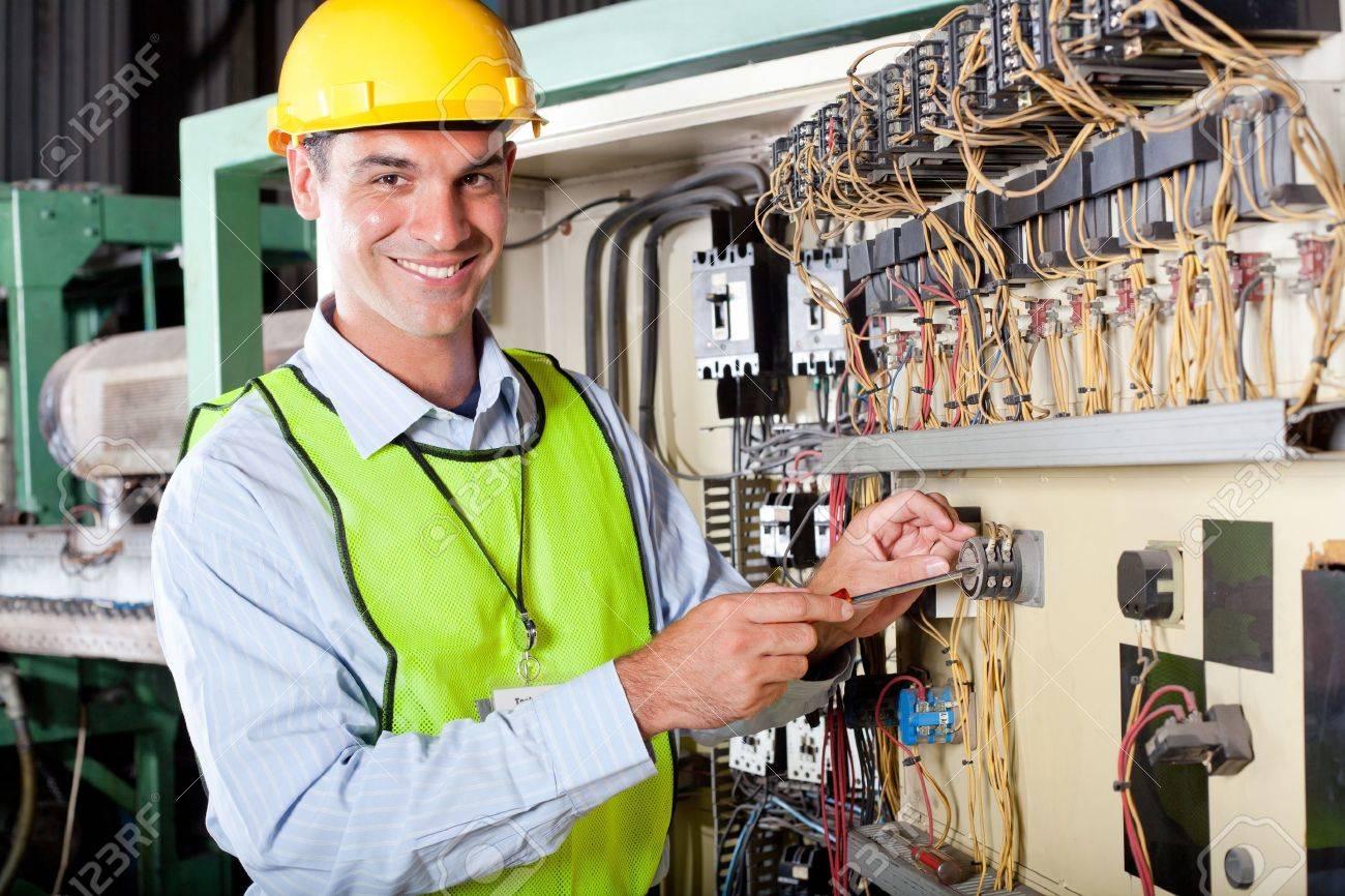 happy male caucasian technician repairing industrial machine control box Stock Photo - 12431764
