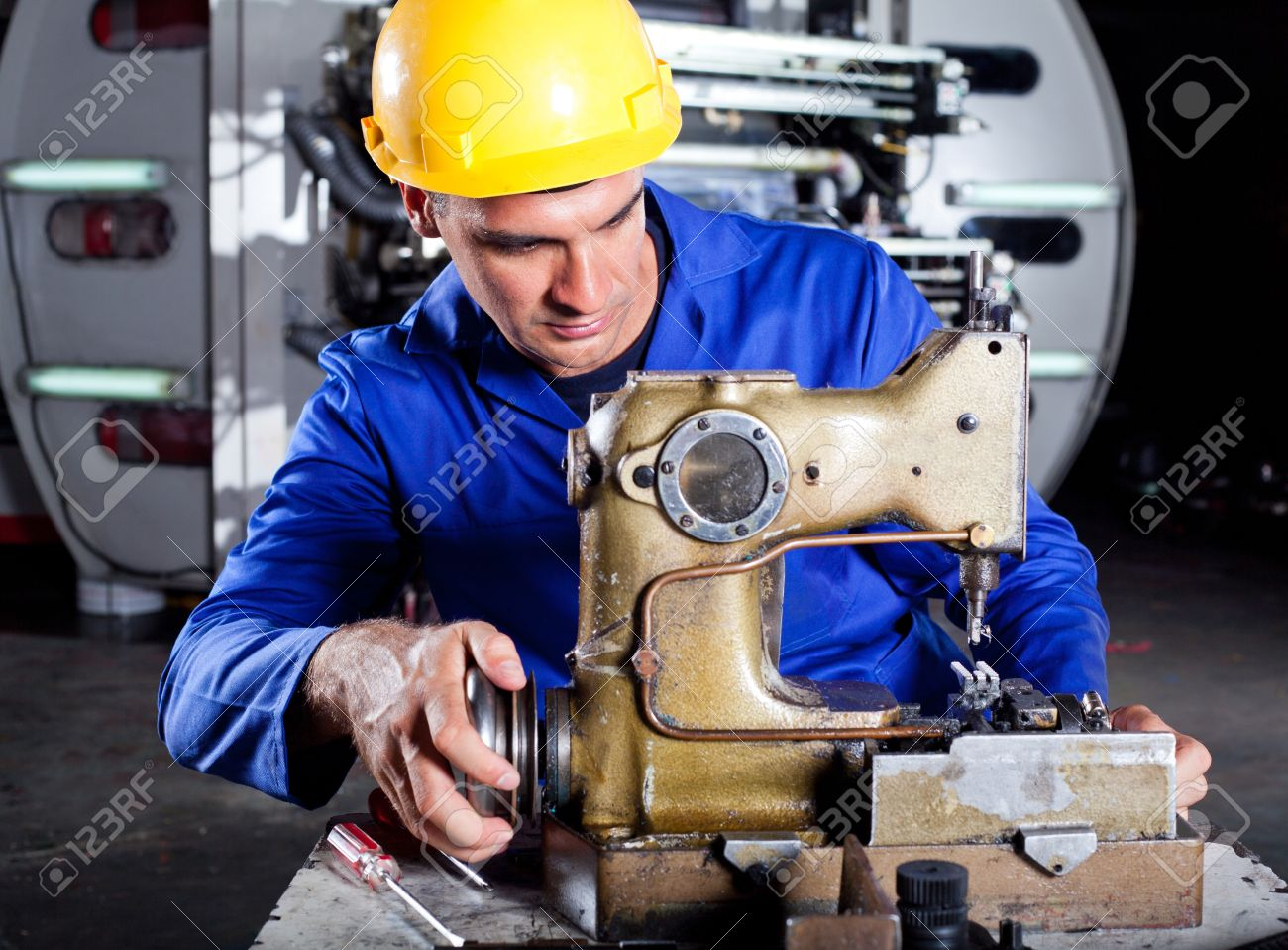Male Technician Fixing Industrial Sewing Machine In Factory Stock ...