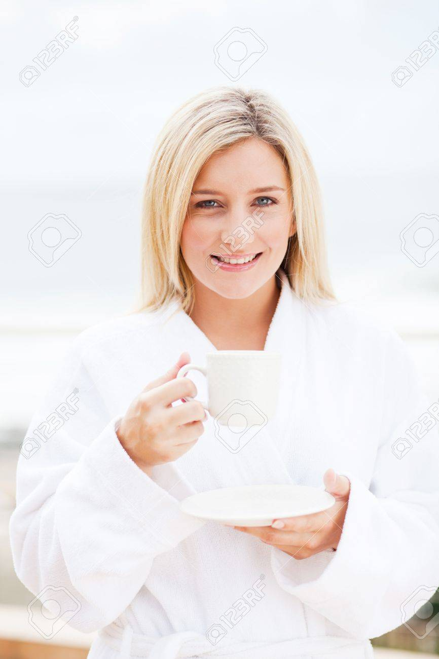 happy young woman in bathrobe drinking coffee in the morning Stock Photo - 12725763