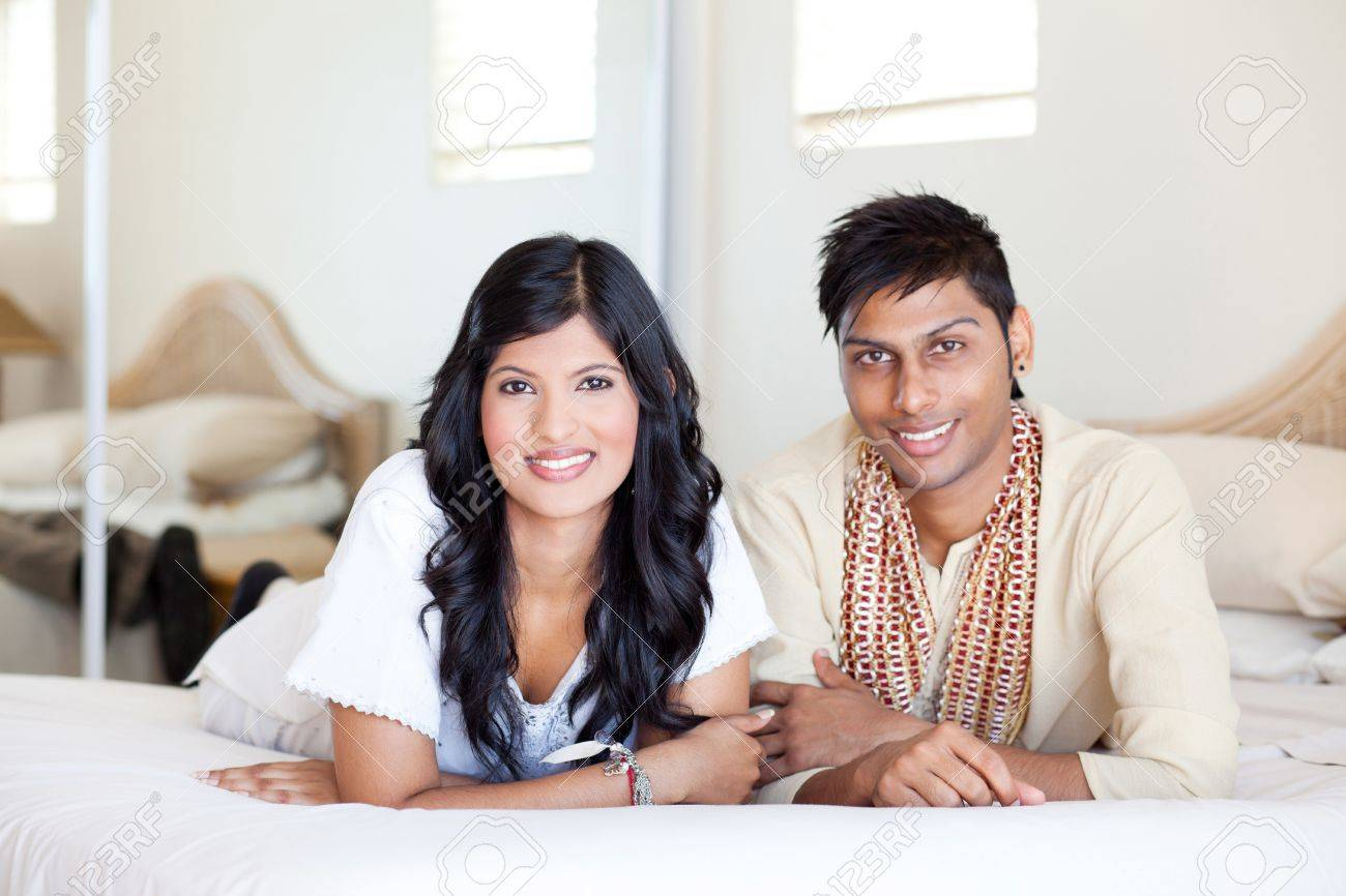 happy young indian couple lying on bed Stock Photo - 12763342