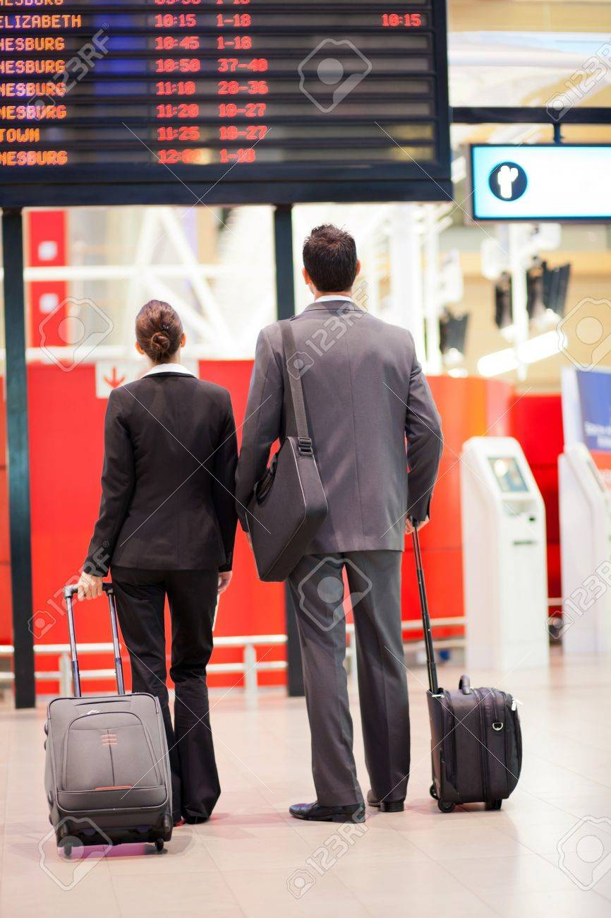 two business travellers looking at airport information board Stock Photo - 12897786
