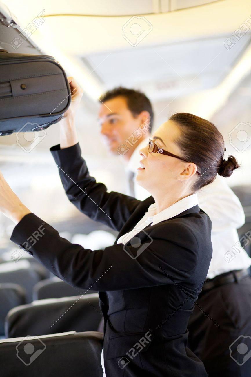 friendly flight attendant helping passenger carry on luggage stock photo friendly flight attendant helping passenger carry on luggage
