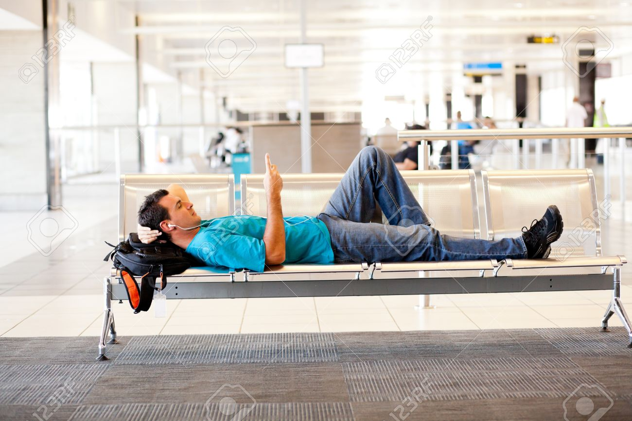 young man lying on airport chairs and resting Stock Photo - 12880796