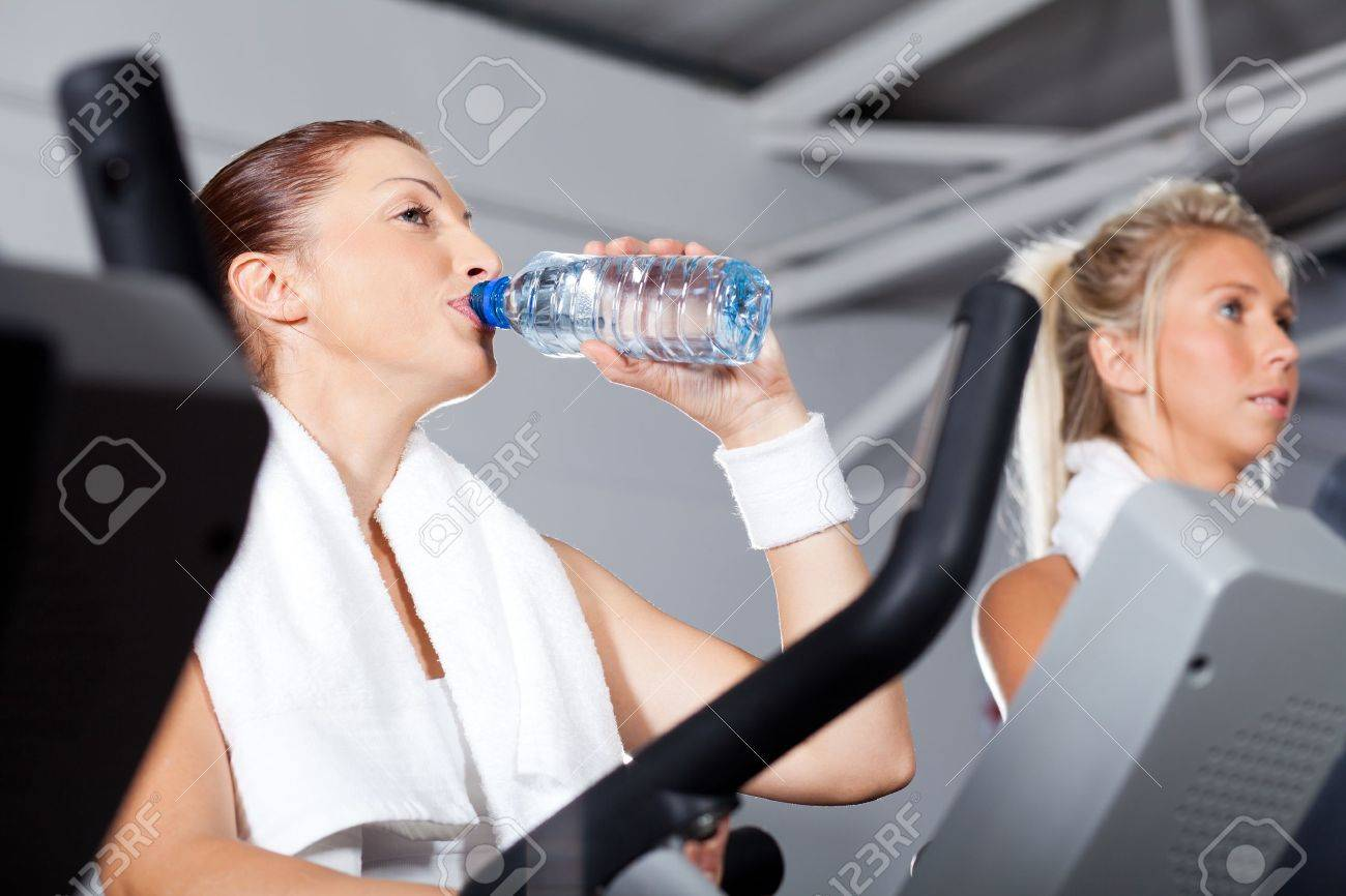 Young woman drinking water while exercising in gym stock photo young woman drinking water while exercising in gym stock photo 13737891 sciox Gallery