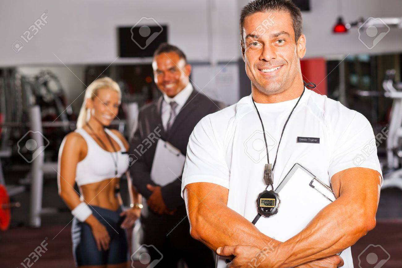 muscular senior gym trainer portrait with colleagues in background Stock Photo - 13829275