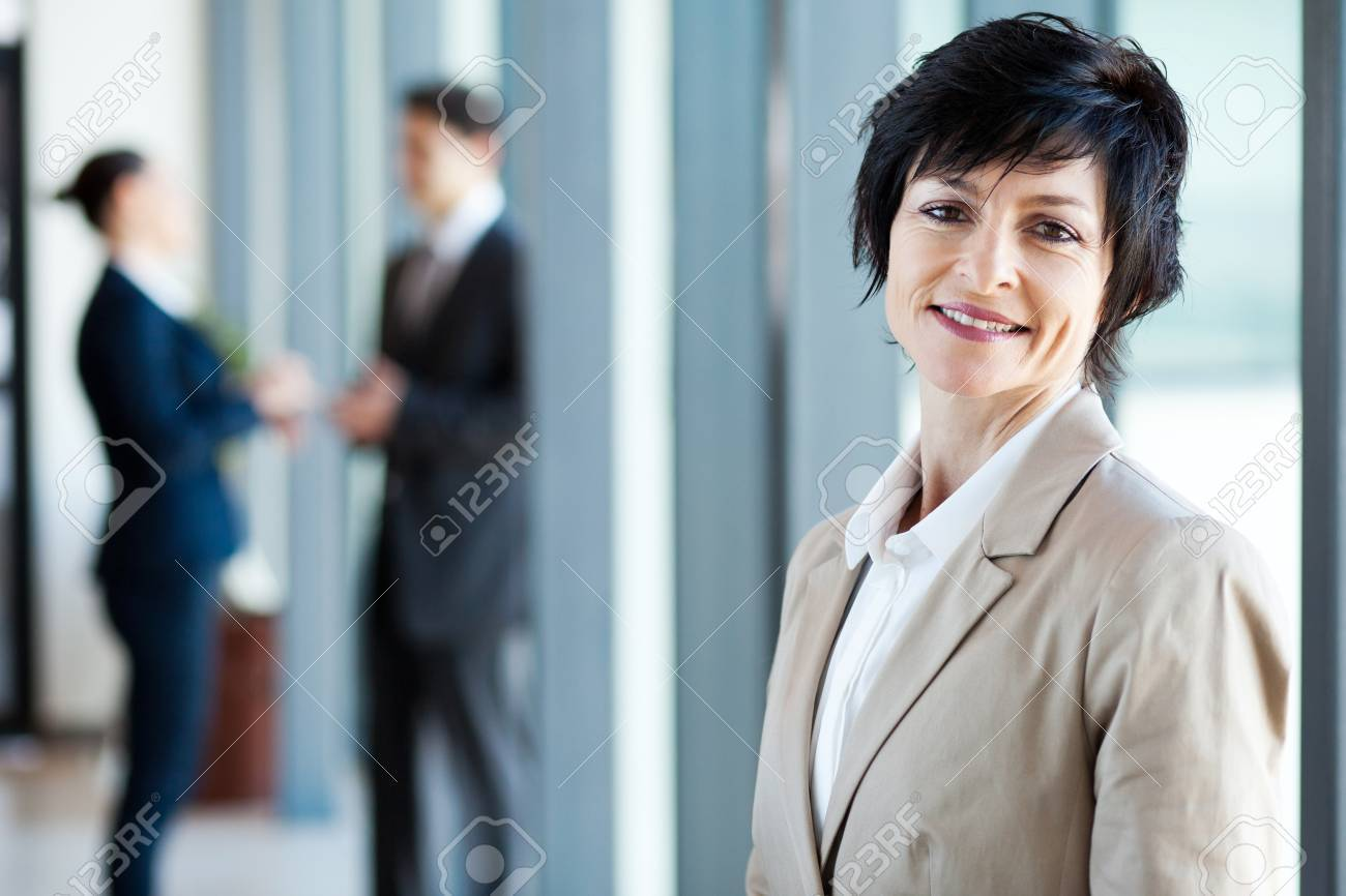 middle aged businesswoman in office with colleagues at background Stock Photo - 14898966