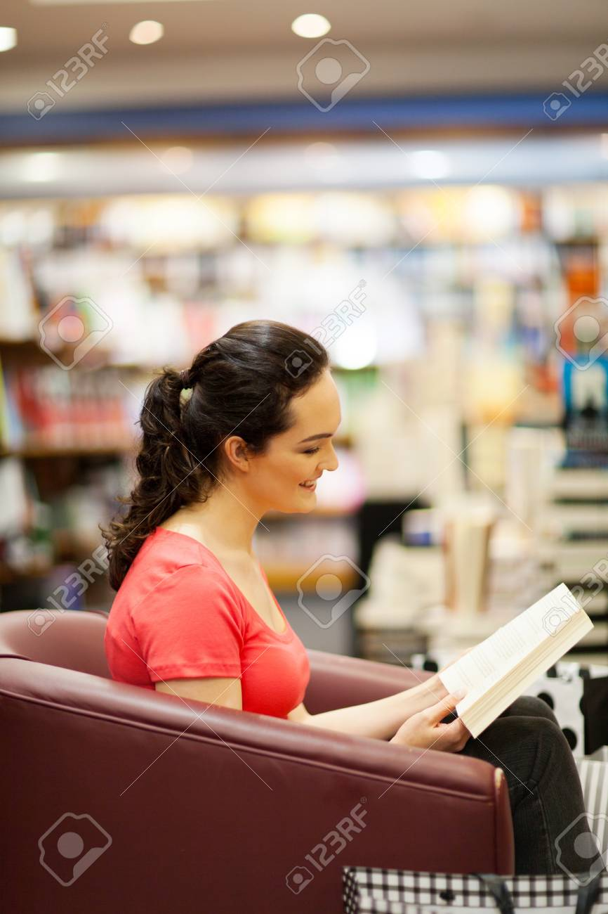 young woman reading a book in bookstore Stock Photo - 15402600