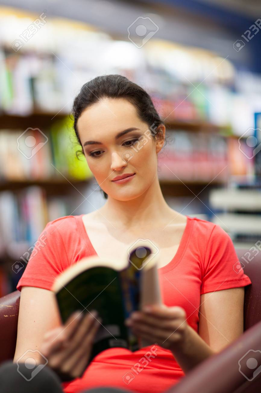 young woman reading book in library Stock Photo - 15401600