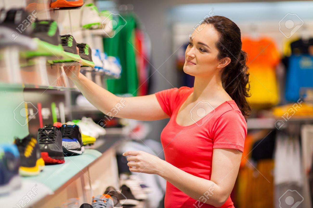 young female sportswear shop assistant working in store Stock Photo - 15402531