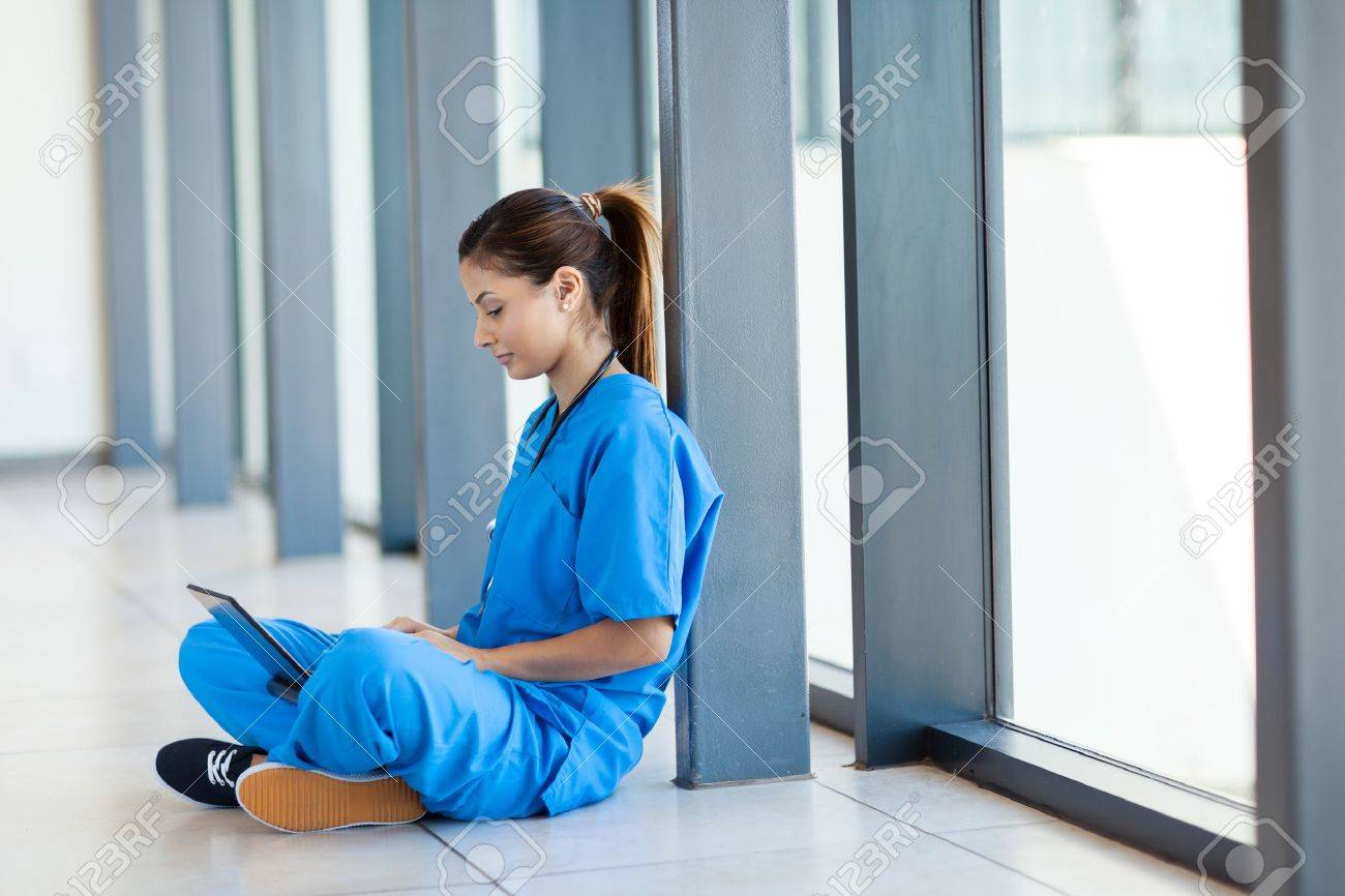 pretty nurse sitting on floor and using laptop computer during break Stock Photo - 15692934