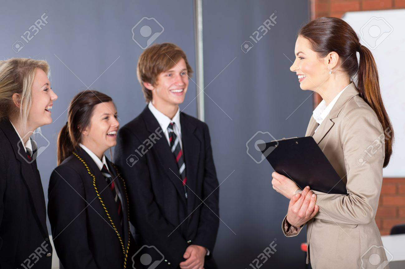 happy high school teacher talking to students in classroom Stock Photo - 15893347
