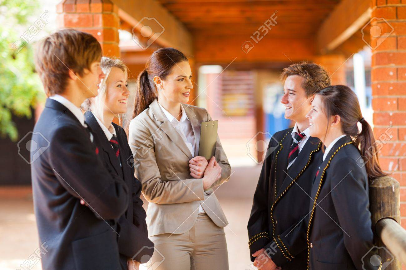 high school teacher talking to students in corridor stock photo