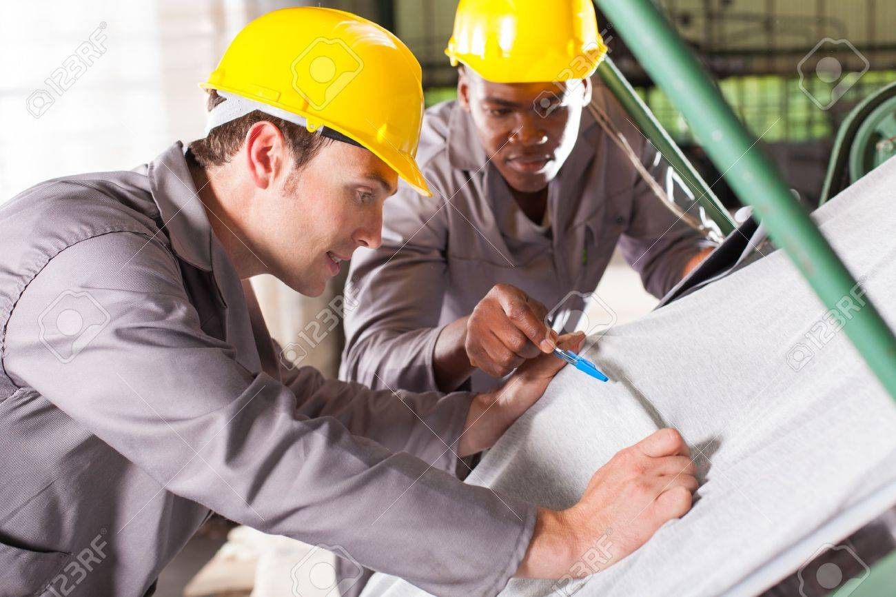 two textile workers checking fabrics quality on QC table Stock Photo - 16013880