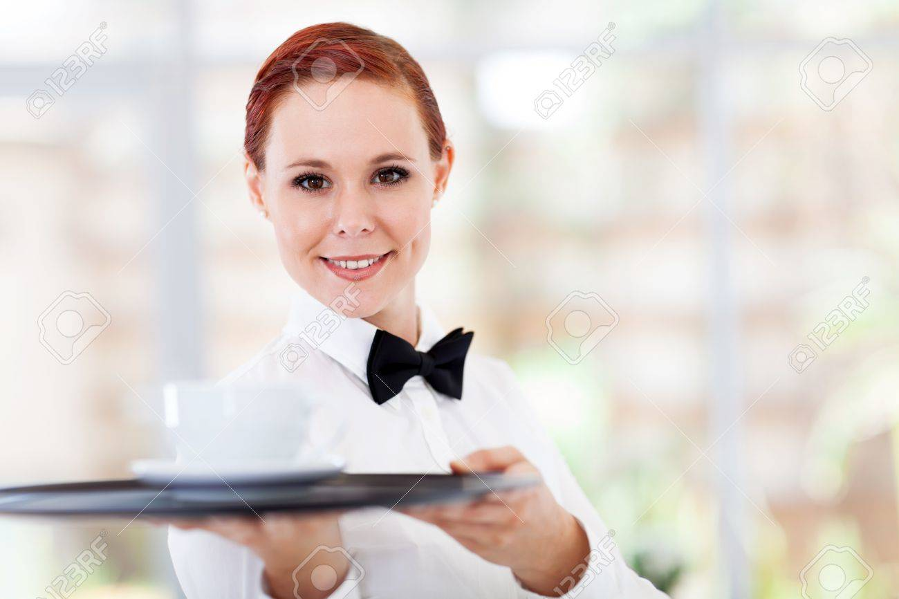attractive young waitress serving coffee in cafe stock photo  - attractive young waitress serving coffee in cafe stock photo