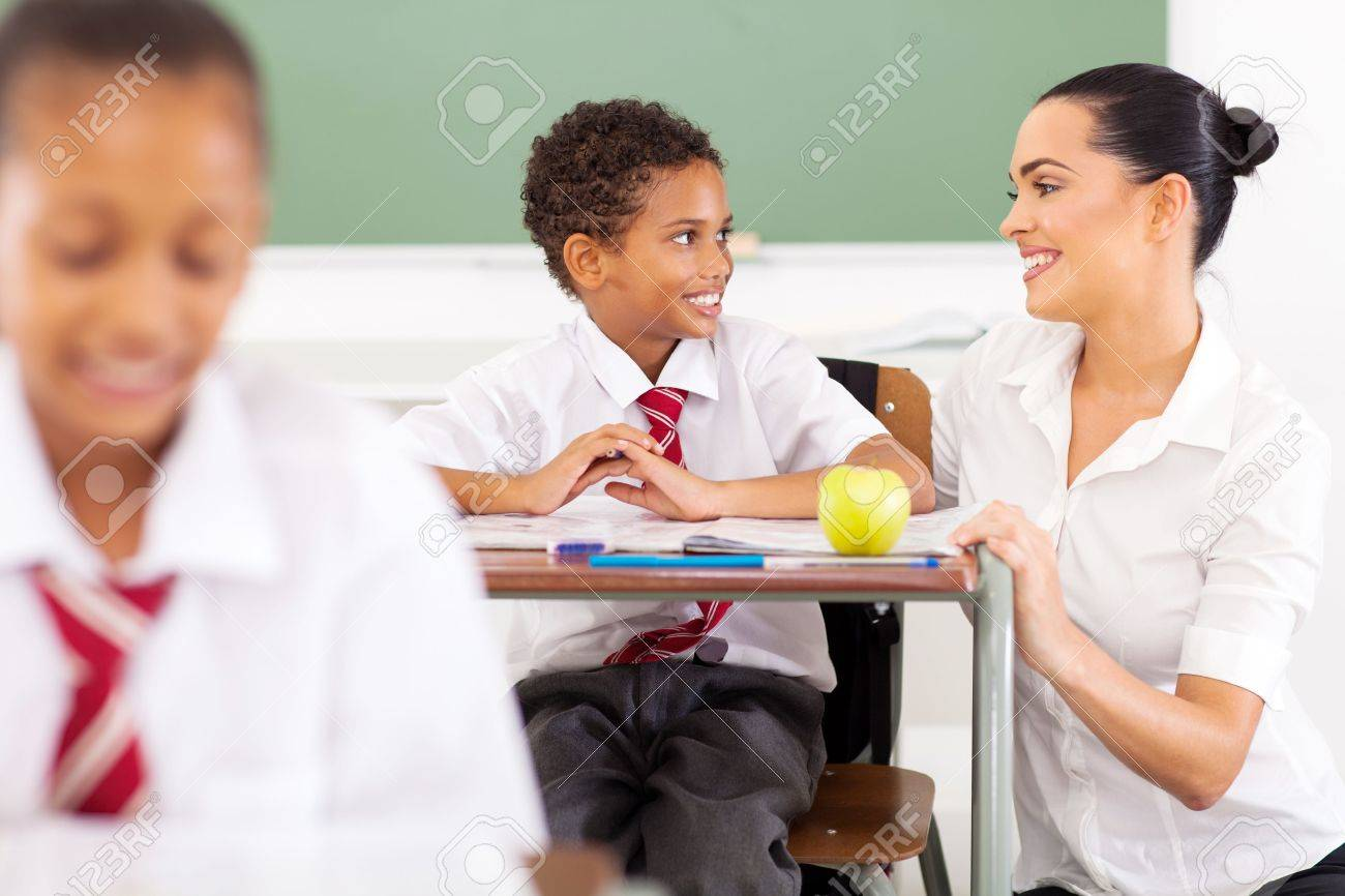 caring elementary school teacher talking to a student in classroom