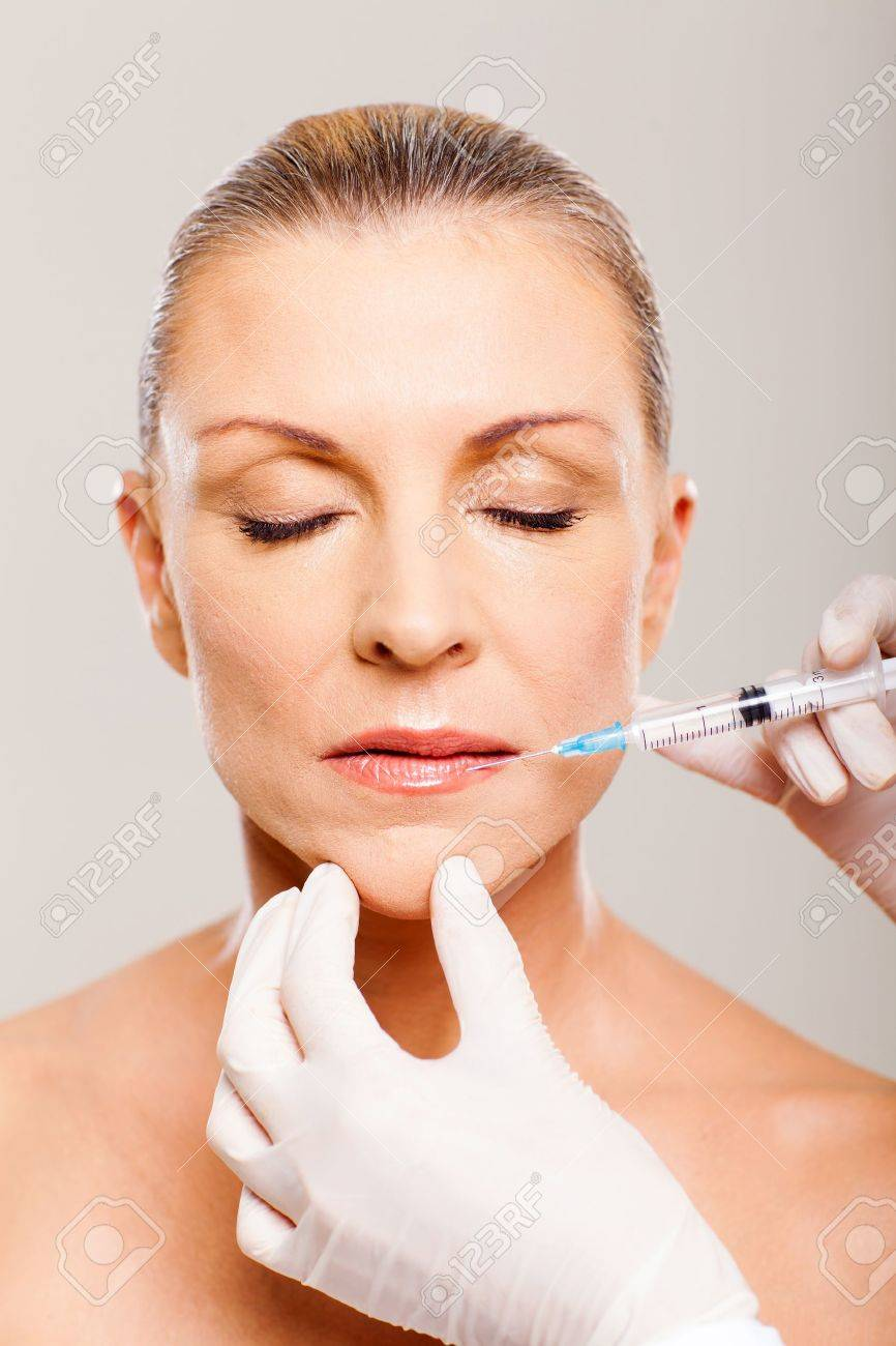 pretty mature woman receiving cosmetic injection on her lips Stock Photo - 18661288