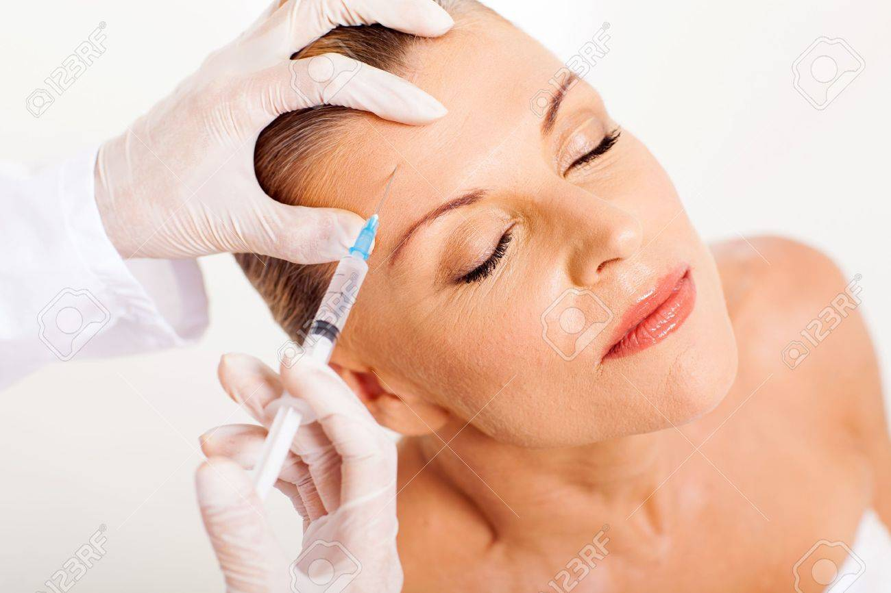 doctor giving face lifting injection on mature woman Stock Photo - 18661260