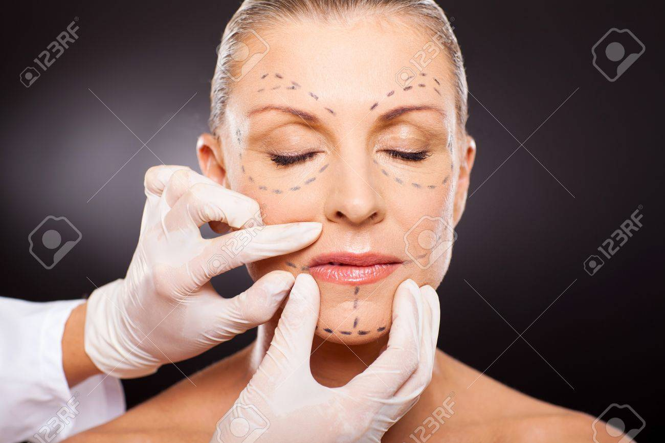 doctor hands on mid age woman before cosmetic surgery Stock Photo - 18661311