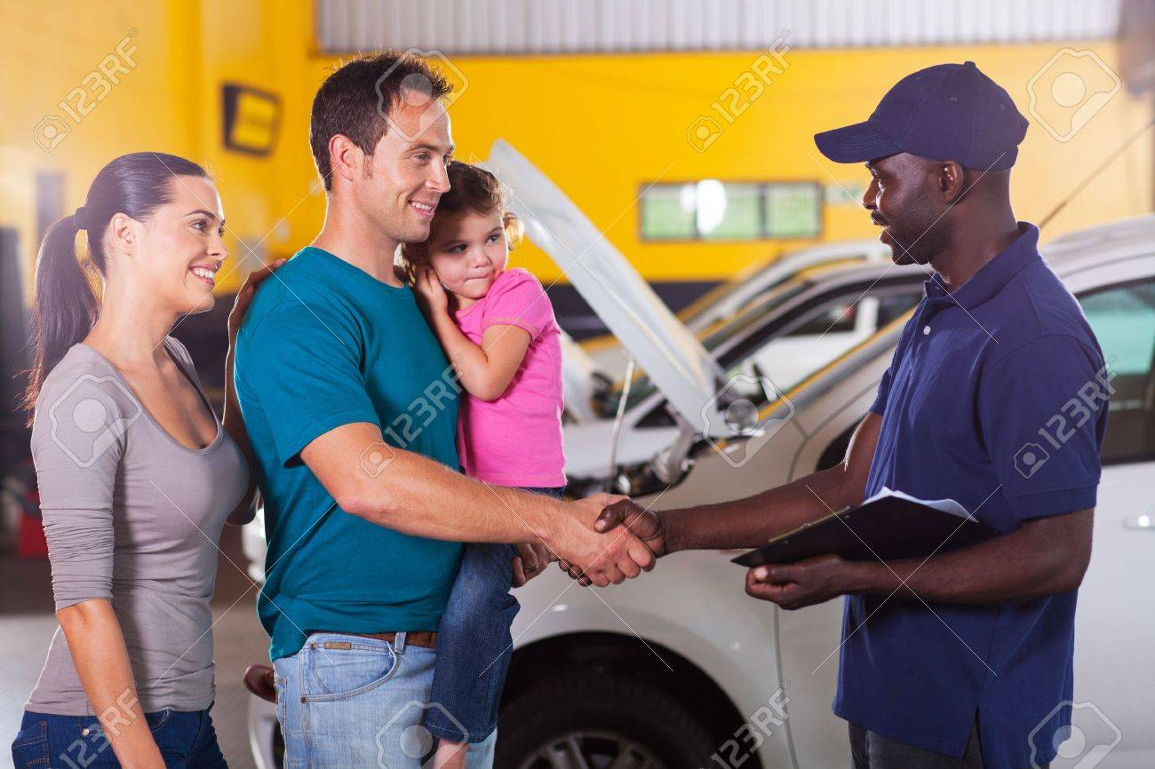 friendly auto mechanic handshaking with family inside workshop Stock Photo - 19202490