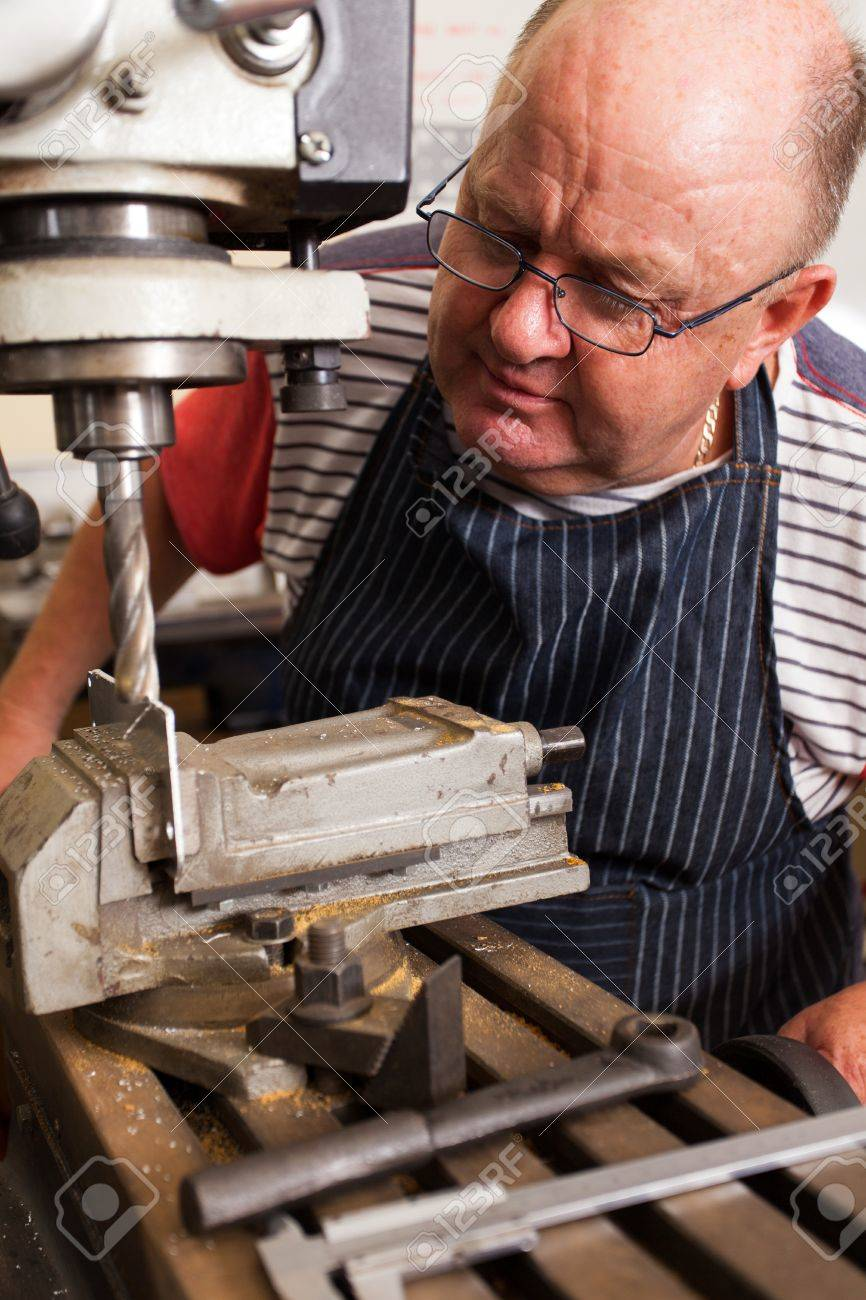 senior man using industrial drilling machine in workshop Stock Photo - 19360968