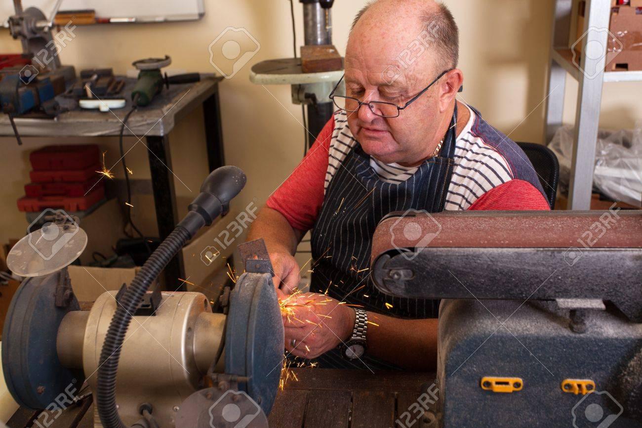 senior man using grinding machine in workshop Stock Photo - 19361011