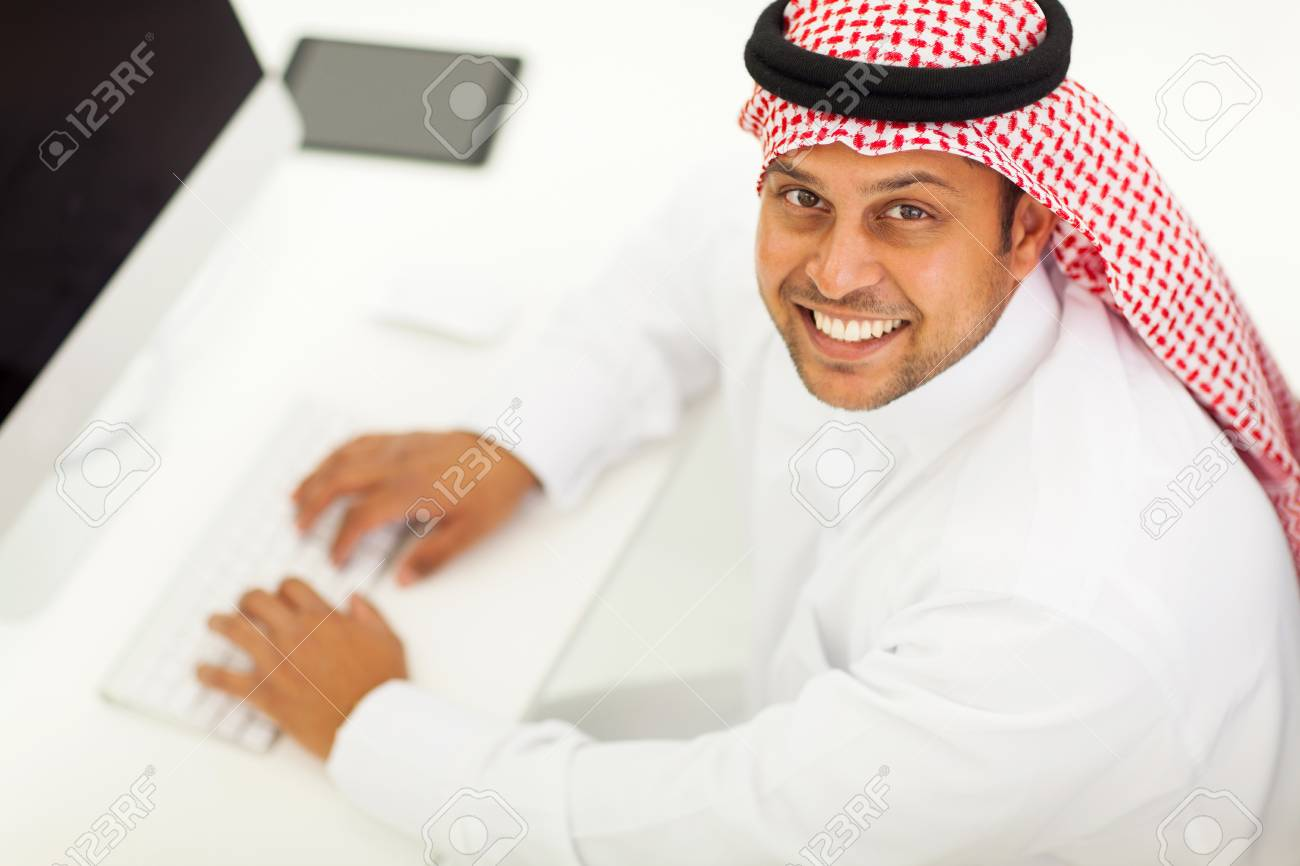 overhead view of a cheerful arabic businessman using modern computer Stock Photo - 19637509