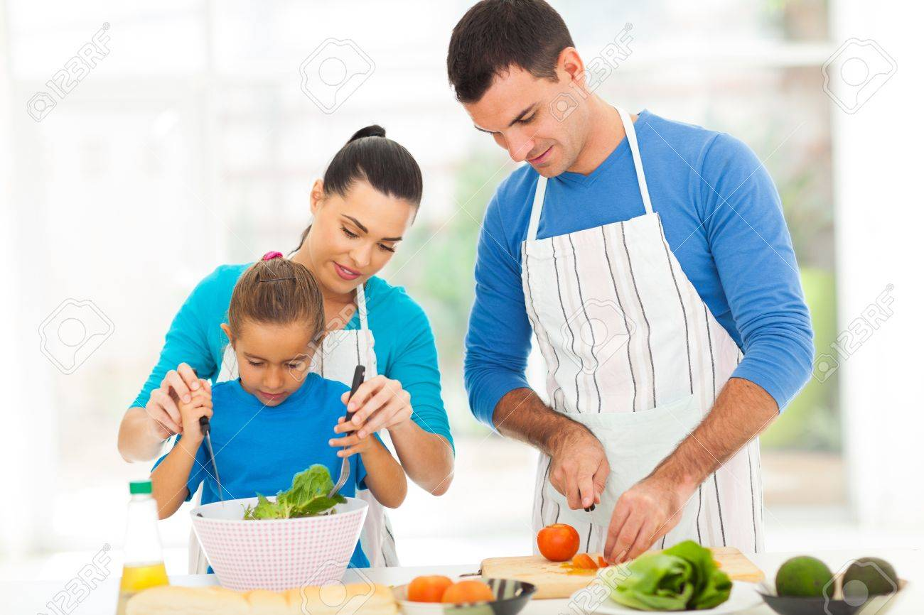 Mother Teaching Little Daughter Mixing Salad When Family Cooking In Kitchen  Stock Photo   19668784
