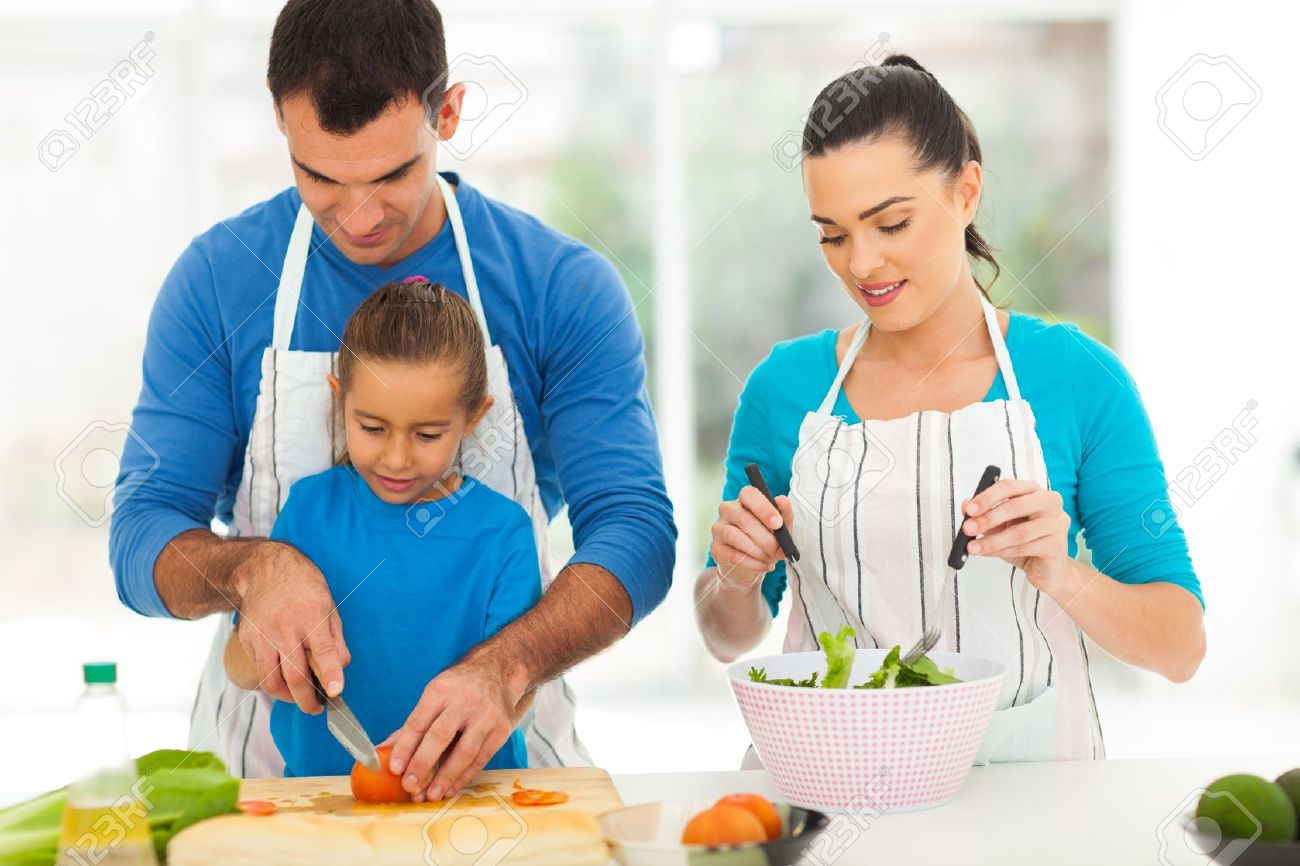 caring father teaching little daughter cutting vegetables while family cooking at home Stock Photo - 19668782