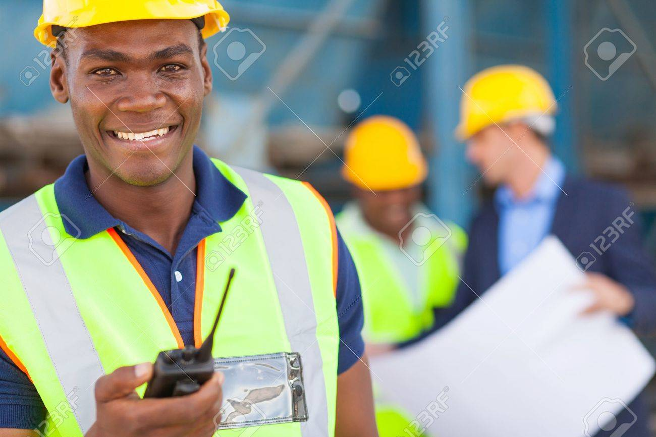happy african american industrial worker with walkie talkie on site with colleagues Stock Photo - 20022642