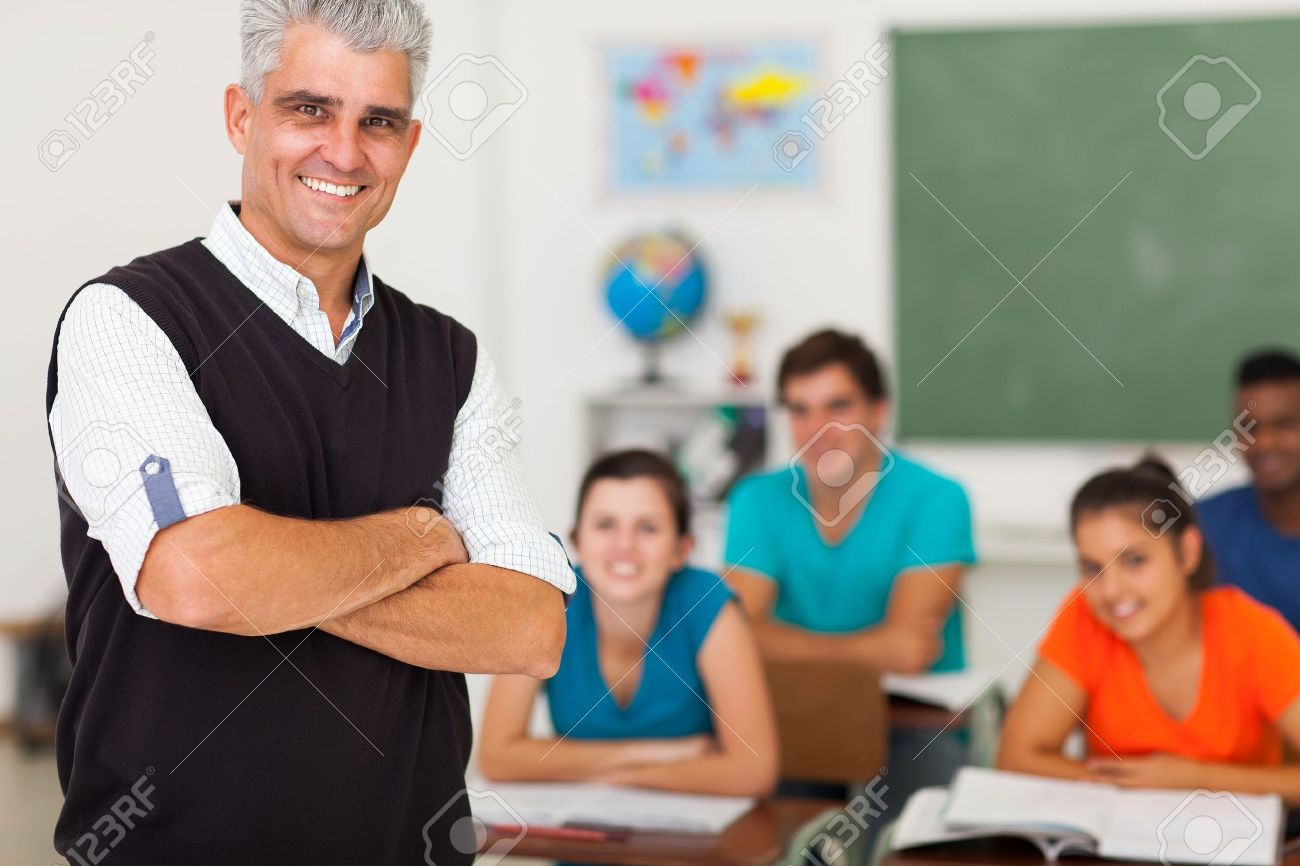 Smiling Middle Aged High School Teacher With Arms Folded Standing ...