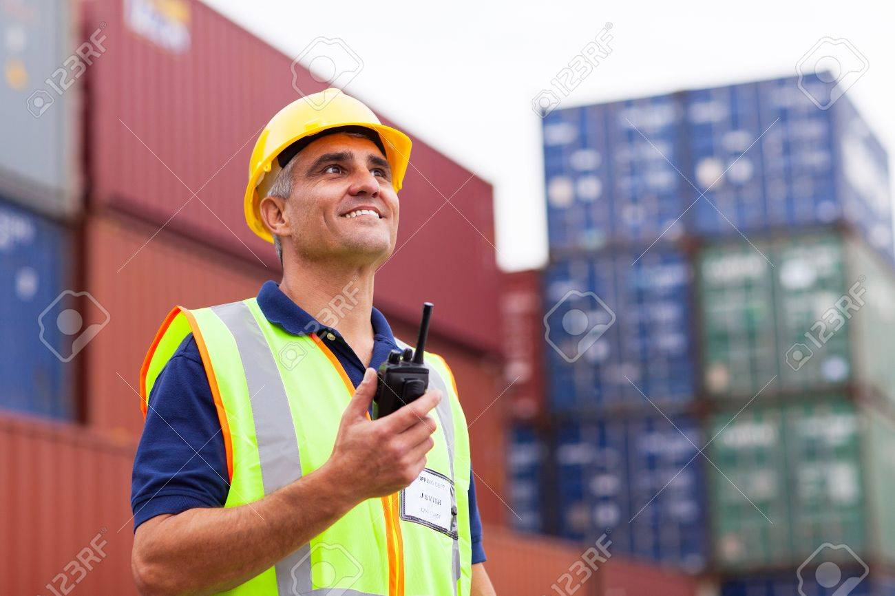 smiling middle aged warehouse worker holding radio at container yard Stock Photo - 20659475