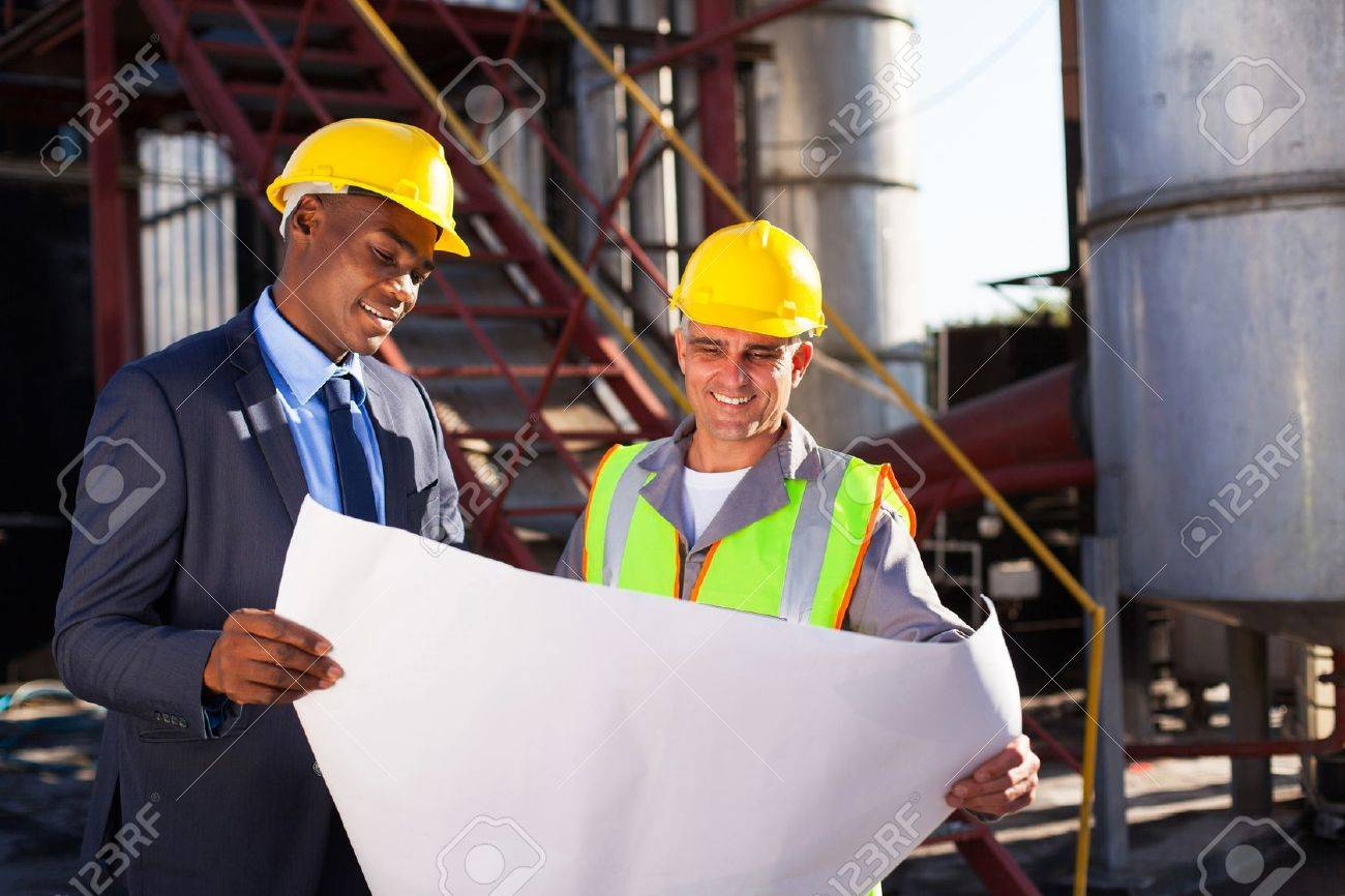 industrial engineers standing in front of a large oil refinery machinery with blueprint on hand Stock Photo - 20659500