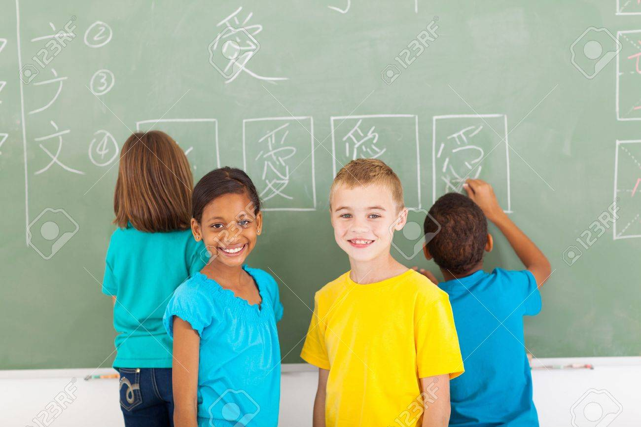 cheerful elementary school students after writing chines on chalkboard Stock Photo - 21191569