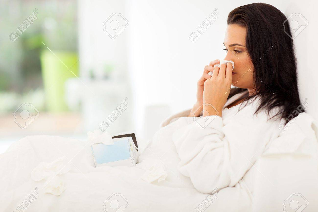 sick woman in bed blowing her nose Stock Photo - 21291059